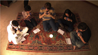five people sit on rug each playing Ocarina on iPhones